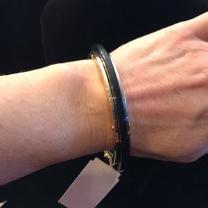 Gold bracelet, with black band accent.